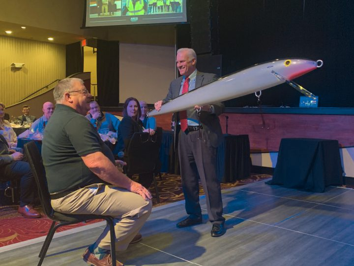 Rob Steigerwald presenting Bill Mace with a giant fishing lure as he prepares for retirement